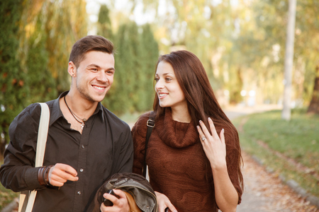 young couple walking in park talking smiling photo