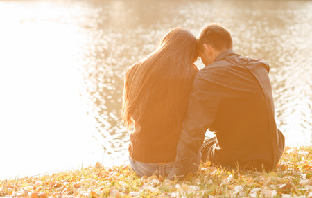 young couple sitting near lake in evening heads together rear view Stock Photo - 24714793