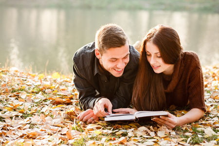 jonge mannelijke en vrouwelijke liggen in de buurt van lake leesboek