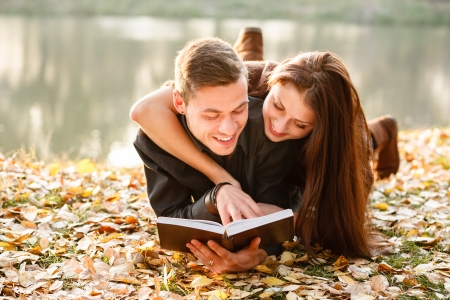 book boy: young couple lying down near lake reading book smiling