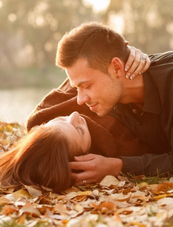 young couple lying down near lake kissing photo
