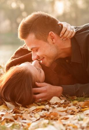 young couple lying down near lake kissing photo