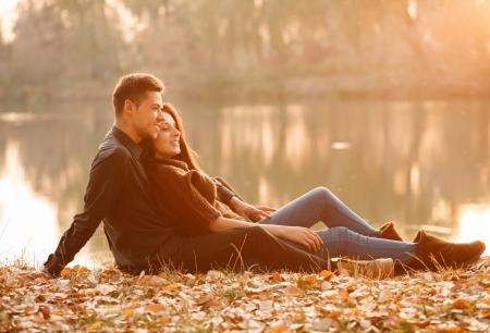 mujer alegre: joven pareja sentada cerca del lago sonriente con una buena vez la puesta del sol