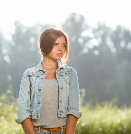portrait of beautiful teenage girl outdoors in jeans wear looking away photo