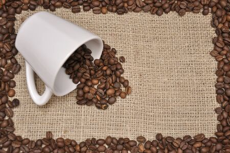 Coffee beans in white cup on rag cloth