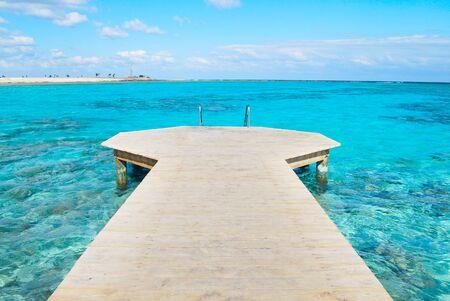 Wooden pier in blue water Imagens