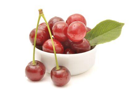 Cherry fruits in white bowl Imagens