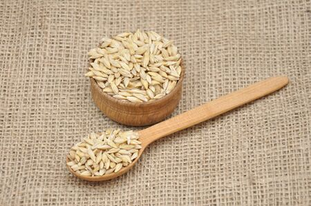 Barley in wooden bowl on a sackcloth.