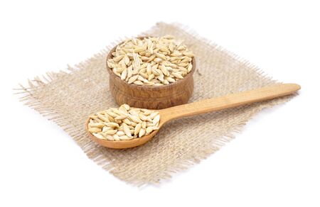 Barley in small wooden bowl isolated on white background
