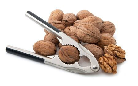 Walnuts with nutcracker isolated on white background