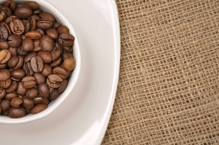 Coffee beans in a white cup on sack cloth.