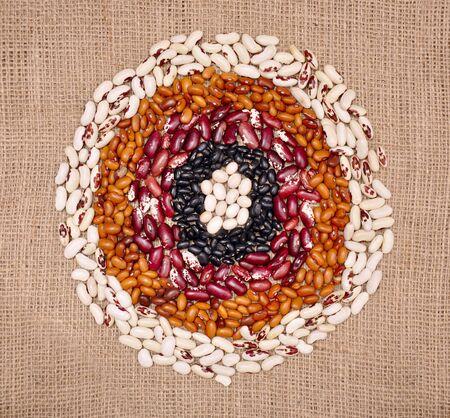 Colored beans. Variations and food circles on sack cloth. Zdjęcie Seryjne
