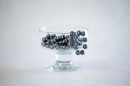 flaunt: A shiny black pearl necklace in a glass.