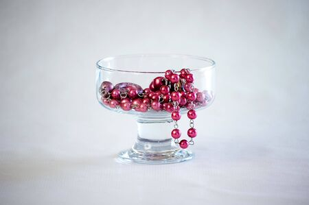 flaunt: A shiny pearl necklace in a glass.