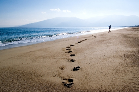 footprint sand: A young woman walking alone at the beach, throwing a stone at the sea.