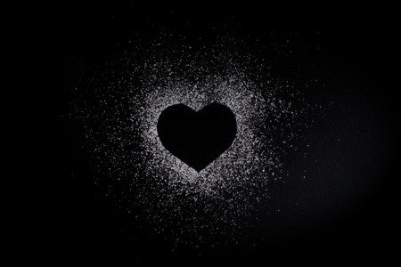 Heart shape made of icing sugar on total black background with copyspase. Concept of Valentine's day and sweet romantic love