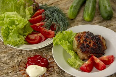 a grilled chicken thigh lies with a lettuce on a plate. On a plate are cut tomatoes, dill and lettuce. whole cucumbers lie on a canvas napkin. dinner in nature. B-B-Q. Stock fotó