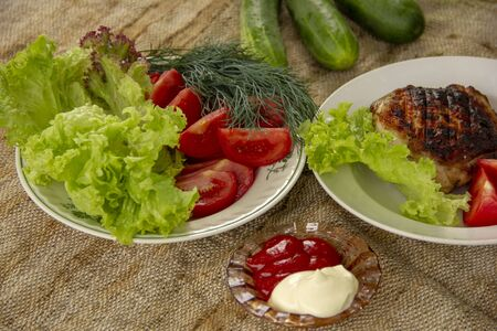 a grilled chicken thigh lies with a lettuce on a plate. On a plate are cut tomatoes, dill and lettuce. whole cucumbers lie on a canvas napkin. dinner in nature.