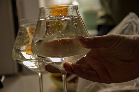 bubbles in the wine. hand holds champagne at an angle.