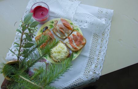 Christmas snack. A light fir tree next to sandwiches and a red candle.