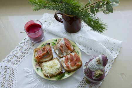 preparation for the new year. festive decor. Christmas tree branch in a vase. on a white napkin sandwiches on a plate.