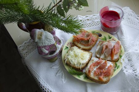 Christmas candlestick. Santa Claus under the Christmas tree. Sandwiches on a white tablecloth. Stok Fotoğraf