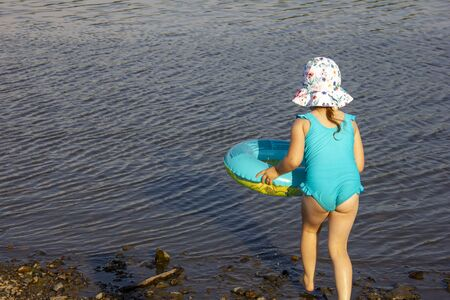 a little girl in panama and a swimsuit bathes in the water in the river.