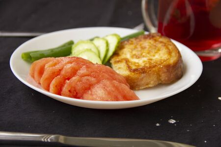 toast fried in a beaten egg lies on a white plate with chopped tomatoes, cucumbers and green onions. Great breakfast. serving dishes on a black tablecloth.