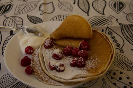 pancakes on a plate with raspberries and sprinkled with powdered sugar. Holiday - Shrovetide.round treat.