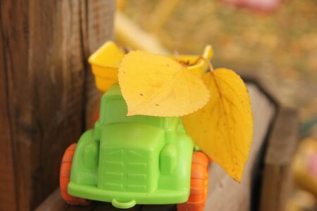children toy green car with orange wheels lucky yellow autumn leaves on wooden background.