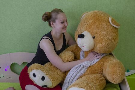 girl with a teddy bear on the bed in the room