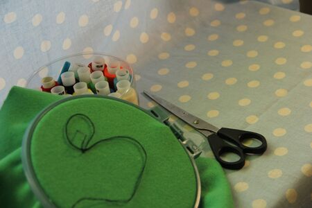 set for embroidery on a blue background. The fabric is hooped. the needle is stuck in the fabric.