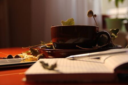 Great autumn background. in a brown mug are dry oak leaves and acorns. Nearby lies a phone - a smartphone and a notepad.