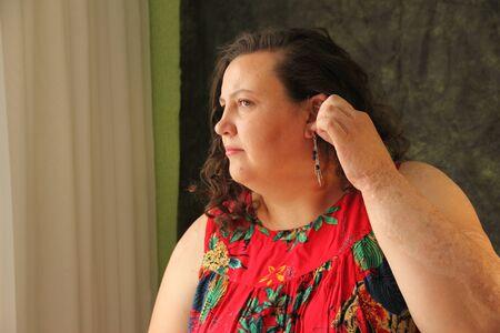 fat woman in a red dress dresses earrings. Model size plus
