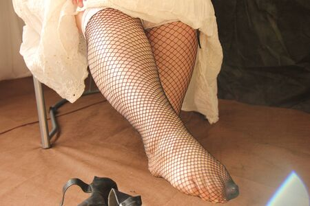 female legs in stockings are stretched forward. Fatigue and heaviness in the legs after a working day.