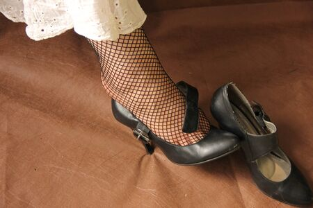 female legs in stockings. High-heeled shoes - one is dressed, the other lies nearby.