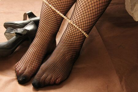 female legs in stockings, pearl beads draped over them. next to high-heeled shoes.