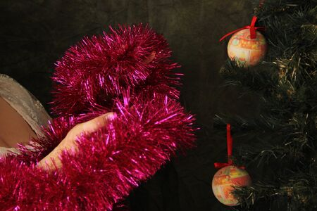 Fat woman decorates a Christmas tree. Joy of the upcoming holiday. Tree Decor. Zdjęcie Seryjne