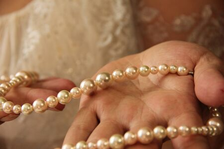 female hands hold pearl beads. On her hands scars from burns.