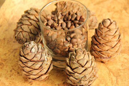 Siberian pine nuts in a glass jar on the wood background. Zdjęcie Seryjne