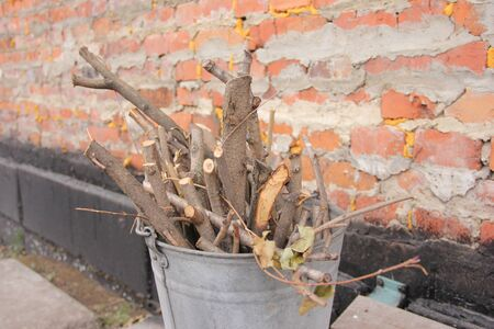 brushwood in a bucket for a stove or fireplace near a brick wall. Old firewood basket on a rustic wooden floor.