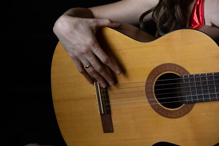 female hands hold an acoustic guitar. play music