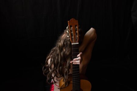 girl in a red dress sits on the floor near the guitar on a black background