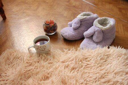 a pair of slippers on the floor next to a mug of tea and a fluffy plaid.