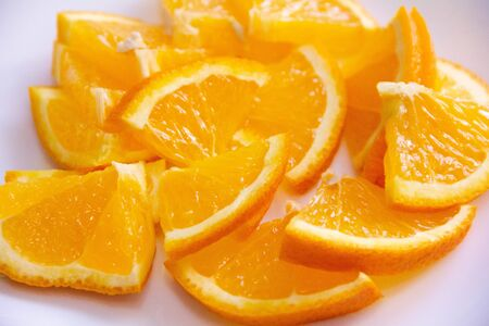 orange wedges cut on a white plate. excellent snacking and richness of vitamins .
