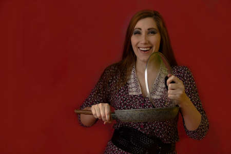 A young sexy woman laughs when she lifts the lid off the pan. She stands against a red background and looks into the frame