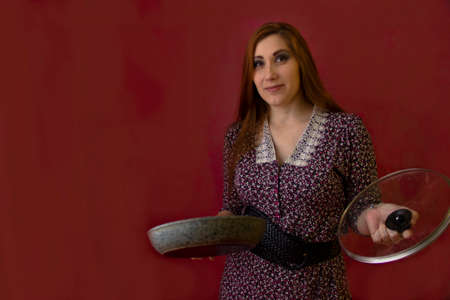 A young sexy woman holds a frying pan and a lid from her. she stands against a red background and looks into the frame Banque d'images