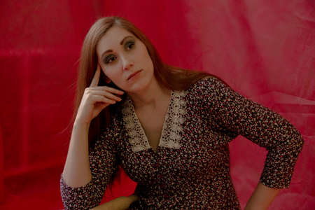 A young sexy woman sits in reverie against a red background. The hand propped up the head. look away