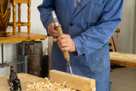 Grey man works chime on wood. carpenters job. Hobby at 60 Фото со стока