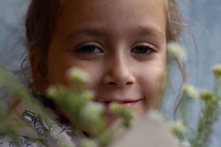 portrait of a cute little girl through the flowers that stick out of the book